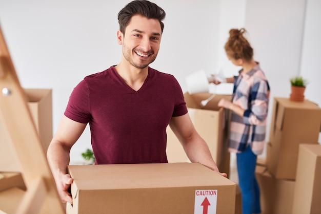 Glimlachende man die naar een nieuw huis verhuist en zijn spullen uitpakt