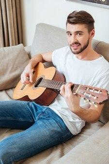 Glimlachende man die op de gitaar op de bank speelt en naar de voorkant kijkt