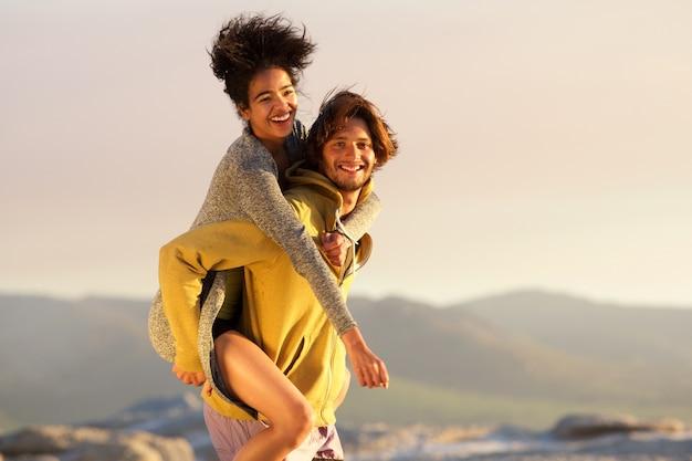 Glimlachende man die piggyback geeft aan mooie jonge vrouw