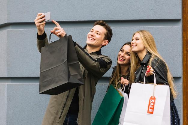 Glimlachende man die selfie met zijn vrouwelijke vriend houden boodschappentassen