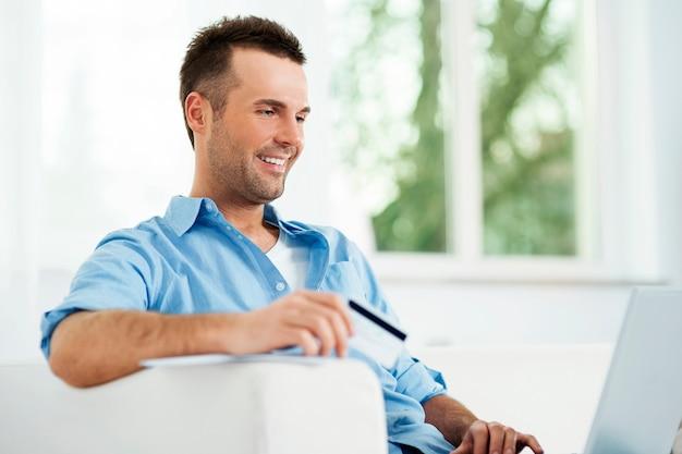 Glimlachende man die van de e-commerce geniet