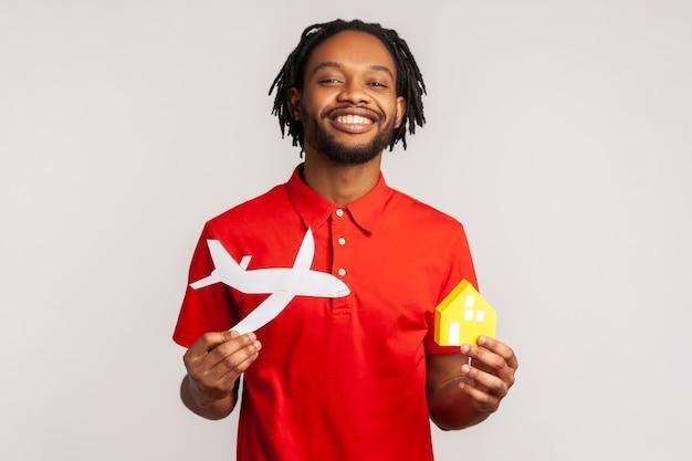 Glimlachende man die van plan is naar het buitenland te verhuizen en appartementen in een ander land te kopen.