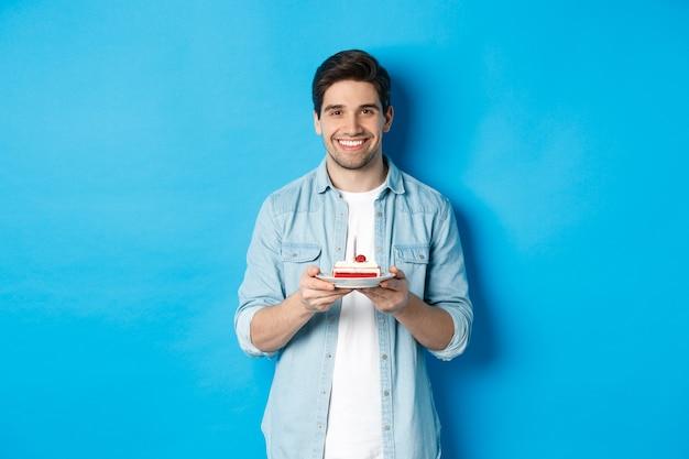 Glimlachende man die verjaardag viert, b-day cake met kaars vasthoudt, staande over blauwe achtergrond.