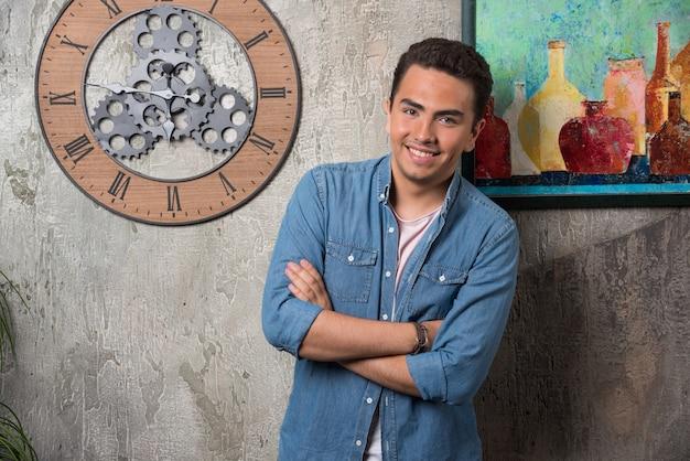 Glimlachende man die zich voordeed op marmeren achtergrond. hoge kwaliteit foto