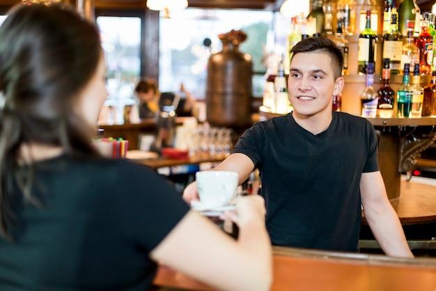 Glimlachende man dienende thee aan vrouw