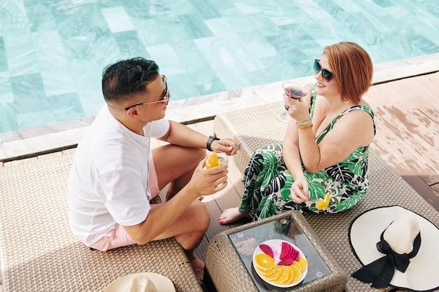Glimlachende man en vrouw cocktails drinken, fruit eten en praten tijdens het rusten bij het zwembad