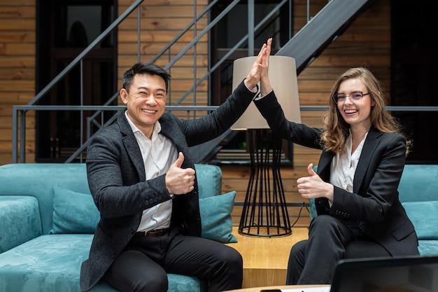 Glimlachende man en vrouw collega's vieren zakelijke overwinning die het doel op de werkplek bereikt en vijf succesvolle