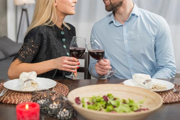 Glimlachende man en vrouw die glazen van drank klinken bij lijst met kom salade en platen