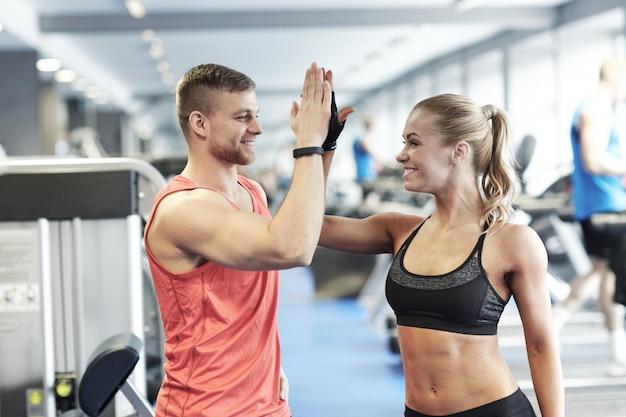 Glimlachende man en vrouw die hoogte vijf in gymnastiek doen