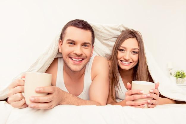 Glimlachende man en vrouw die met deken en hete thee zonnebaden