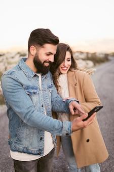 Glimlachende man en vrouw die op telefoon op weg kijken