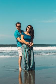 Glimlachende man en vrouw die op waterkant van strand koesteren