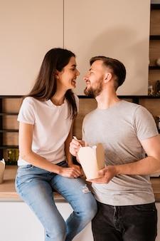 Glimlachende man en vrouw die samen lunch hebben thuis