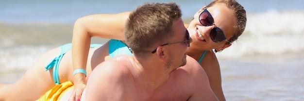 Glimlachende man en vrouw liggen op het strand