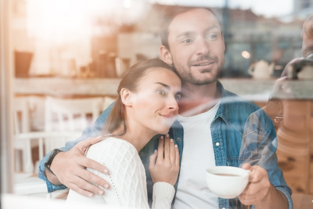 Glimlachende man en vrouw met kop hebben thee in cafe.