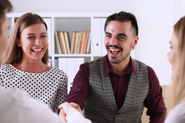 Glimlachende man en vrouw schudden elkaar de hand als hallo op kantoor