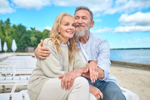 Glimlachende man en vrouw zitten op zee strand