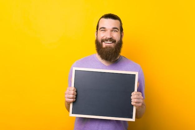 Glimlachende man houdt een klein schoolbord over gele achtergrond.