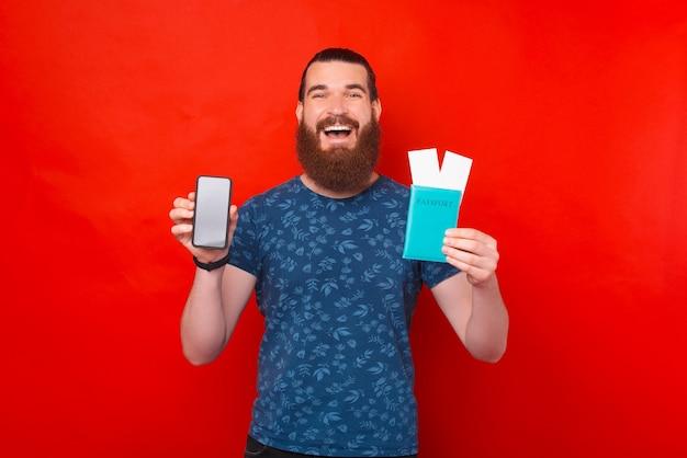 Glimlachende man houdt paspoort met kaartjes en zijn telefoon.