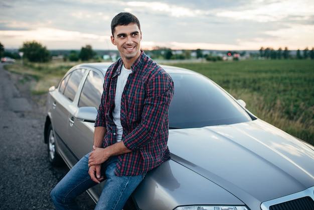 Glimlachende man in de buurt van zijn auto langs de weg in zomerdag, groene natuur