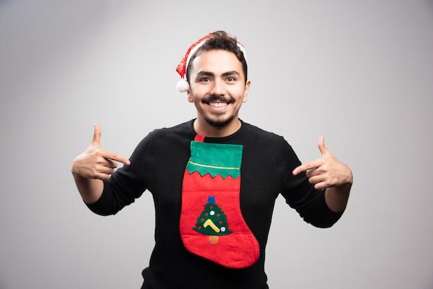 Glimlachende man in de hoed van de kerstman wijzend op zijn trui.