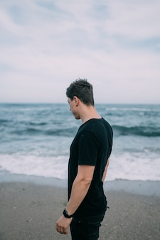Glimlachende man in een zwart t-shirt staat aan de zanderige kust.