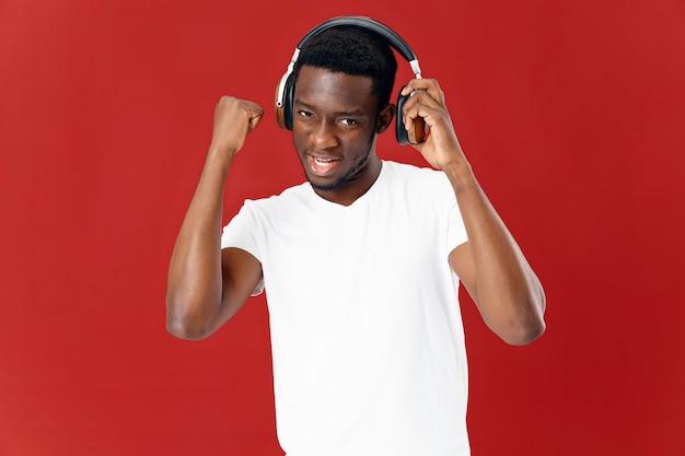 Glimlachende man in koptelefoon luisteren naar muziek in wit t-shirt