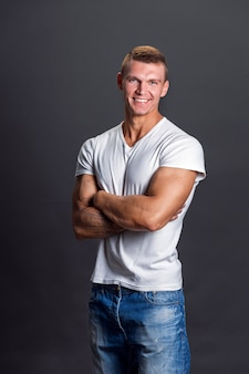 Glimlachende man in lege t-shirt op grijze muur