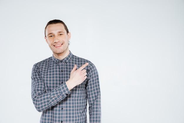 Glimlachende man in overhemd weg wijzen