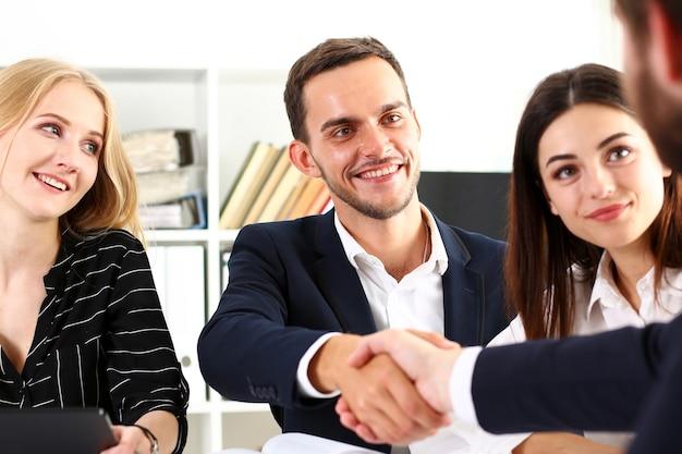 Glimlachende man in pak handen schudden als hallo in kantoor portret.