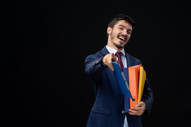 Glimlachende man in pak met verschillende documenten en naar voren wijzend op geïsoleerde donkere muur