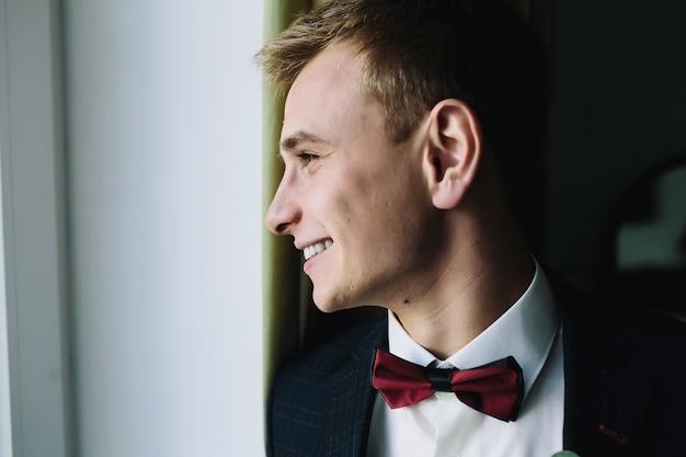 Glimlachende man in pak naar buiten kijken