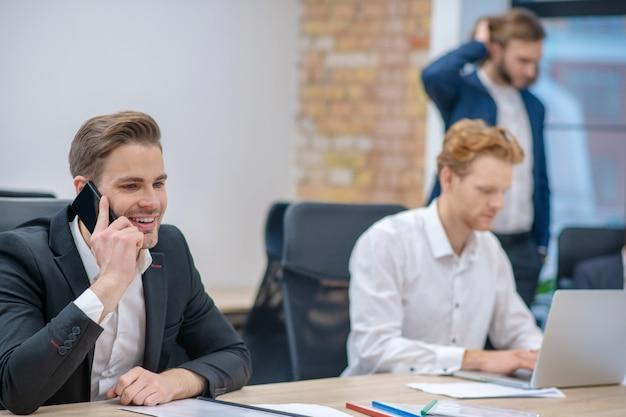 Glimlachende man in pak praten over smartphone zittend aan tafel en werken in de buurt van collega's op kantoor