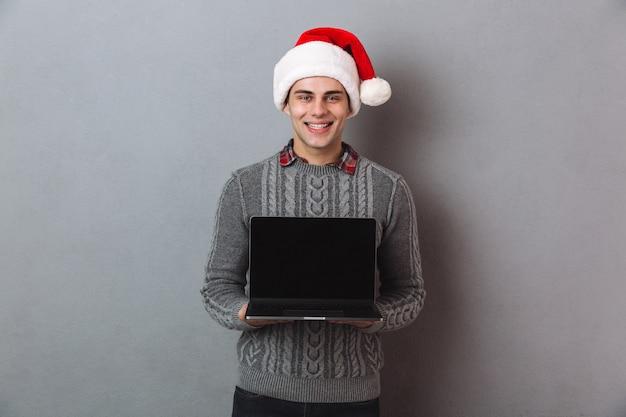Glimlachende man in trui en kerstmuts met lege laptop computerscherm