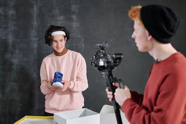 Glimlachende man in vrijetijdskleding met nieuw paar sneakers over open doos voor camera gehouden door zijn vriend tijdens het fotograferen