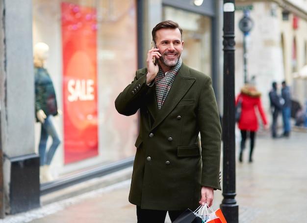 Glimlachende man is aan de telefoon tijdens het winkelen in de winter