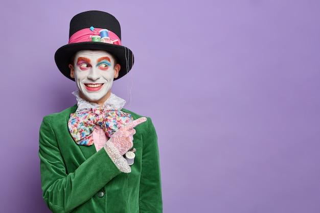 Glimlachende man jurken voor carnaval feest heeft afbeelding van hoedenmaker uit wonderland geeft weg op lege ruimte draagt halloween kostuum en lichte make-up geïsoleerd op paarse muur