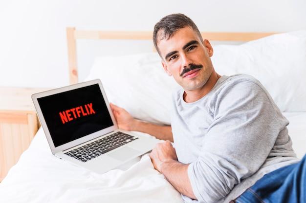 Glimlachende man kijkt naar de camera tijdens het kijken naar netflix shows
