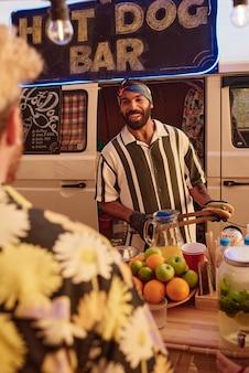 Glimlachende man kookt hotdogs in een speciaal busje buiten voor mensen op een feestje