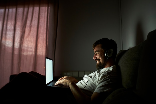 Glimlachende man laat thuis werken. hij zit in het donker op de bank.
