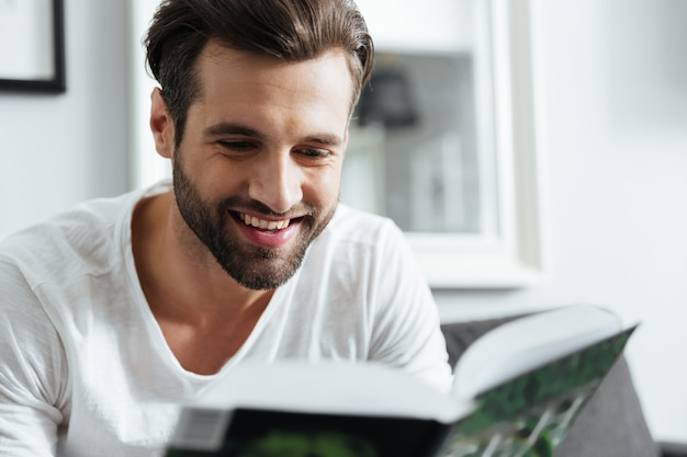 Glimlachende man leesboek. opzij kijken.