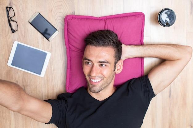 Glimlachende man liggend op vloer en met selfie foto