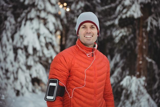 Glimlachende man luisteren naar muziek in koptelefoon van slimme telefoon