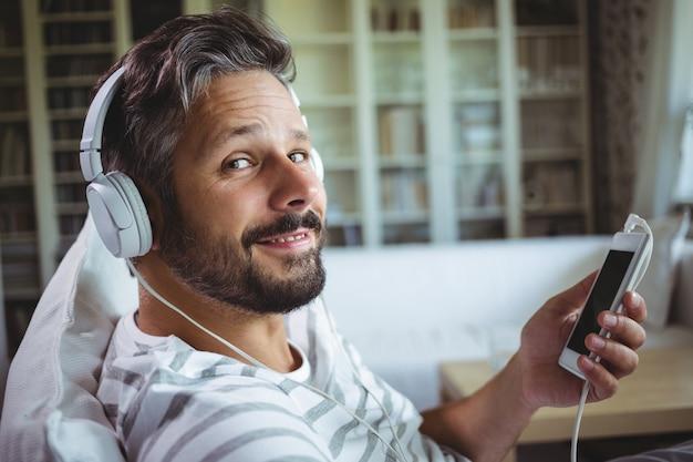 Glimlachende man luisteren naar muziek op de koptelefoon
