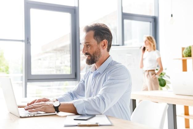 Glimlachende man manager die op laptop computer werkt