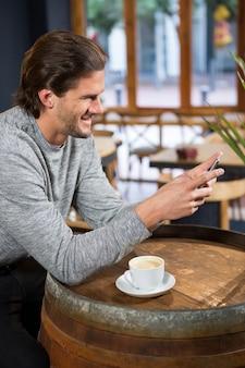 Glimlachende man met behulp van slimme telefoon aan tafel in de coffeeshop