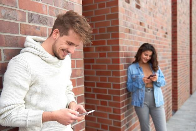 Glimlachende man met behulp van slimme telefoon en vrouw op de achtergrond