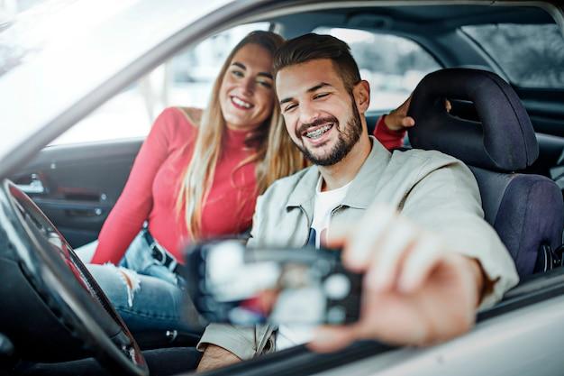 Glimlachende man met beugels en glimlachende vrouw in een auto die een selfie maakt.