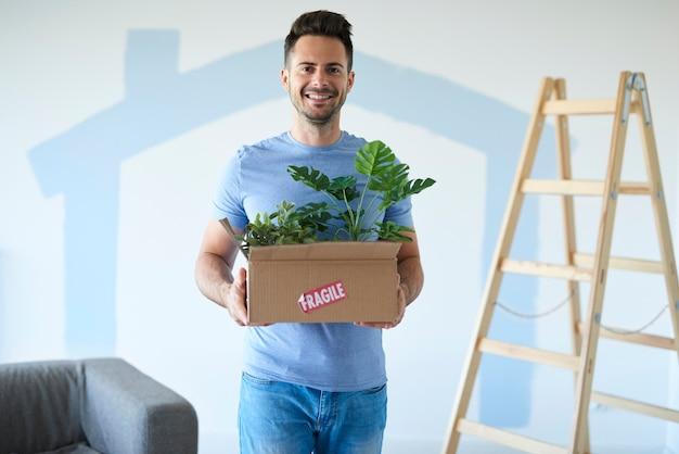 Glimlachende man met bewegende doos met planten in nieuw huis