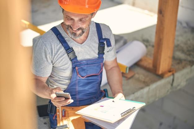 Glimlachende man met blauwdrukken in zijn handen met zijn mobiele telefoon in een half afgebouwd gebouw